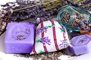 Seife aus Lavendel, daneben ein Lavendelsäckchen und drum herum Lavendel