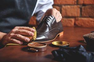 Mann reinigt Schuhe aus Leder.