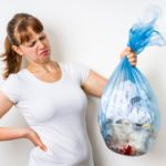 Frau hält angewidert Mülltüte