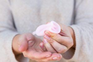 frau faltet eine Menstruationstasse