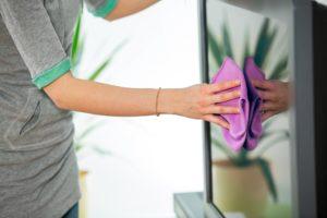 eine frau beim reinigen des fernsehers mit einem mikrofasertuch