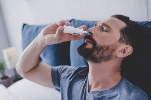 Mann macht Nasenspray Test