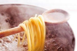 Spaghetti hängen über dem Kochlöffel im Kochenden Wasser