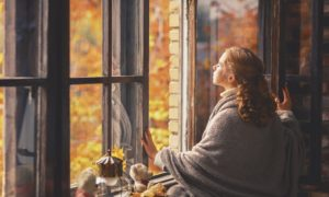 Frau vor offenem Fenster im Herbst
