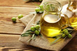 Olivenöl in Glaskaraffe auf einem Tuch.