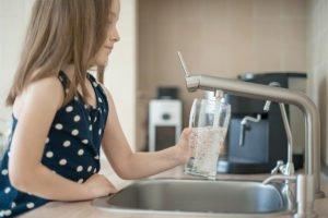 kind fuellt glas aus wasserhahn