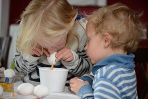 zwei kinder pusten gemeinsam ostereier aus