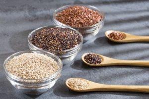 Quinoa auf Löffeln in verschiedenen Farben.