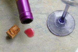 rotweinflasche mit glas und verschuettetem wein auf einem granitboden