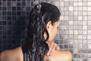 frau waescht sich unter der dusche die haare