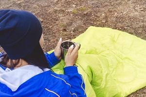 Frau mit Kaffeetasse und Schlafsack.