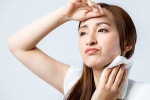 Frau schwitzt im Gesicht und am Hals