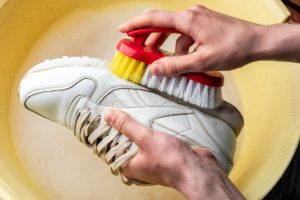 mann waescht seine sneaker mit einer buerste