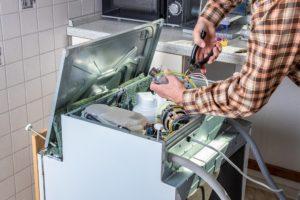 mann repariert seine spuelmaschine
