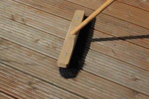 Holzterrasse mit dem Besen reinigen