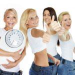 Vier schlanke Frauen tragen zu große Hosen.