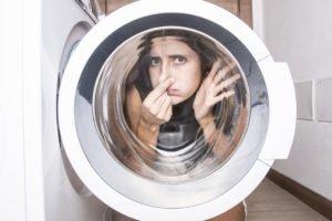 Frau kniet mit zugehaltener Nase hinter der Tür einer Waschmaschine