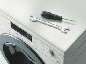 schraubendreher und schraubenschluessel liegen auf einer waschmaschine