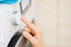 person stellt die waschmaschine ein