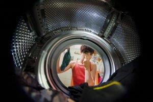 Frau hält sich die Nase beim Blick in die Waschtrommel weil Wäsche nach Waschen stinkt