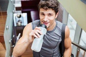 Mann trinkt Wasser beim Sport.