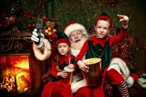 weihnachtsmann mit zwei kindern und einer fernbedienung