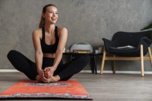 eine frau sitzt auf einer yogamatte